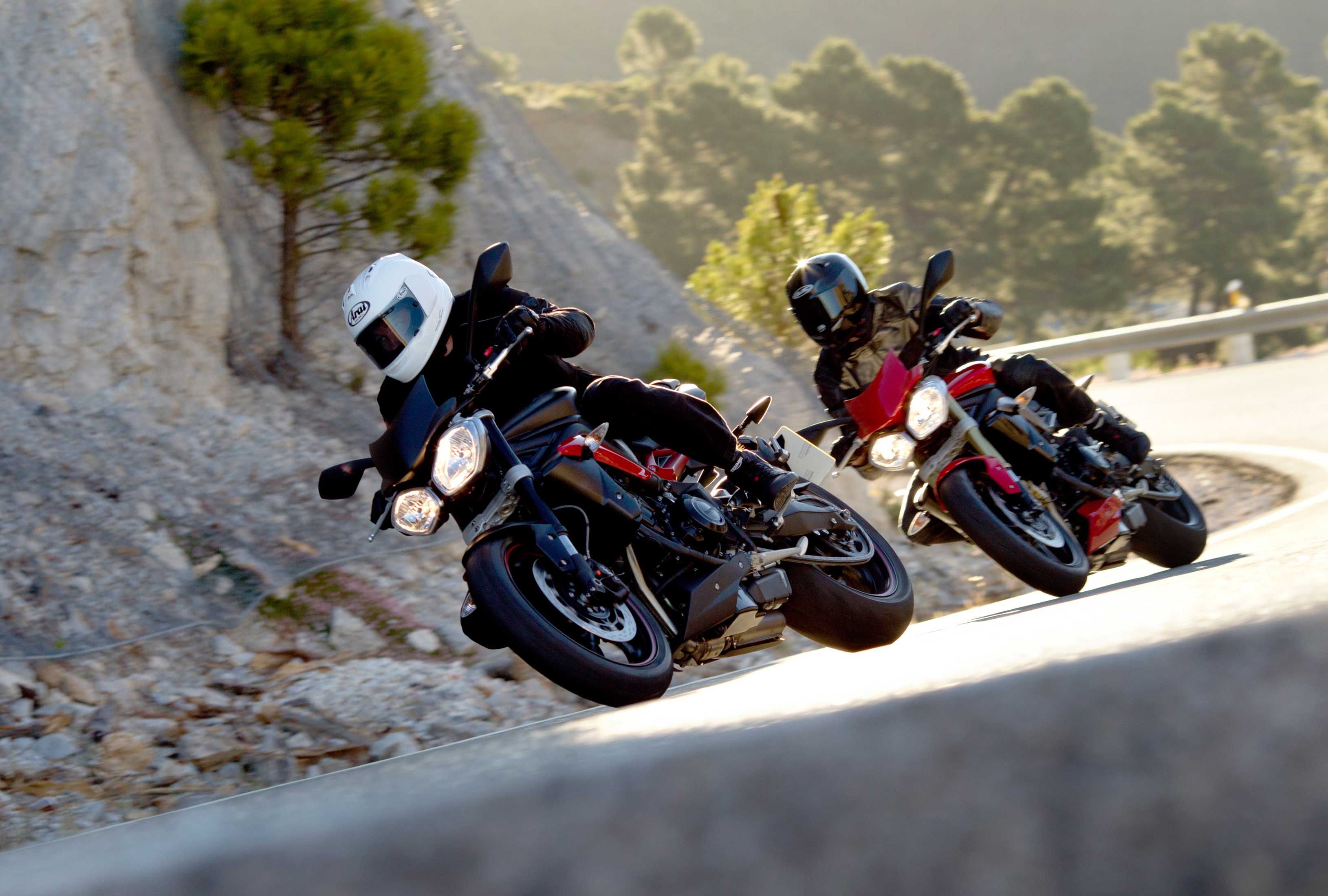 Two Triumph Street Triple R motorcycles cornering a bend