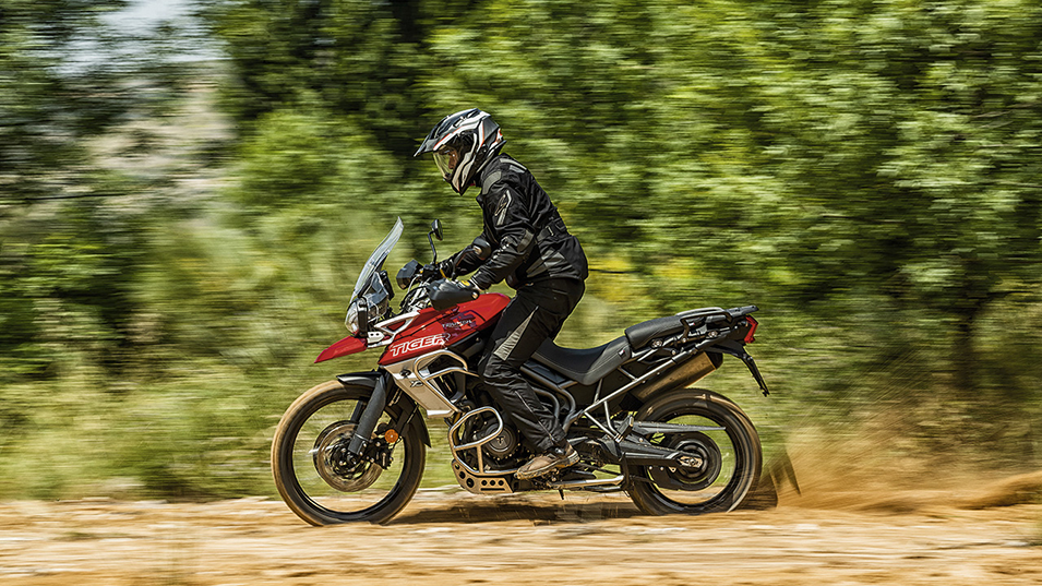 Triumph Tiger 800 XCA in colour red riding with rural background.