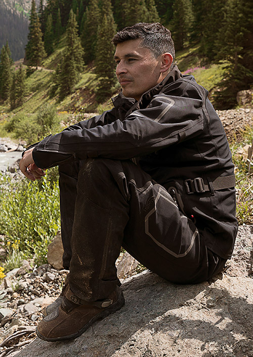 Ernie Vigil sitting by a stream in his Triumph riding jacket and trousers