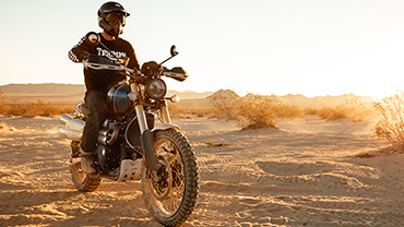 Triumph Scrambler 1200 XE stationary with rider on desert terrain