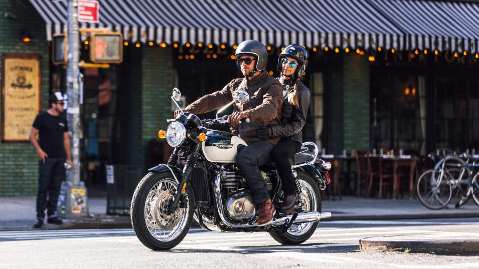 Triumph Bonneville T120 with rider and pillion cruising through an urban setting