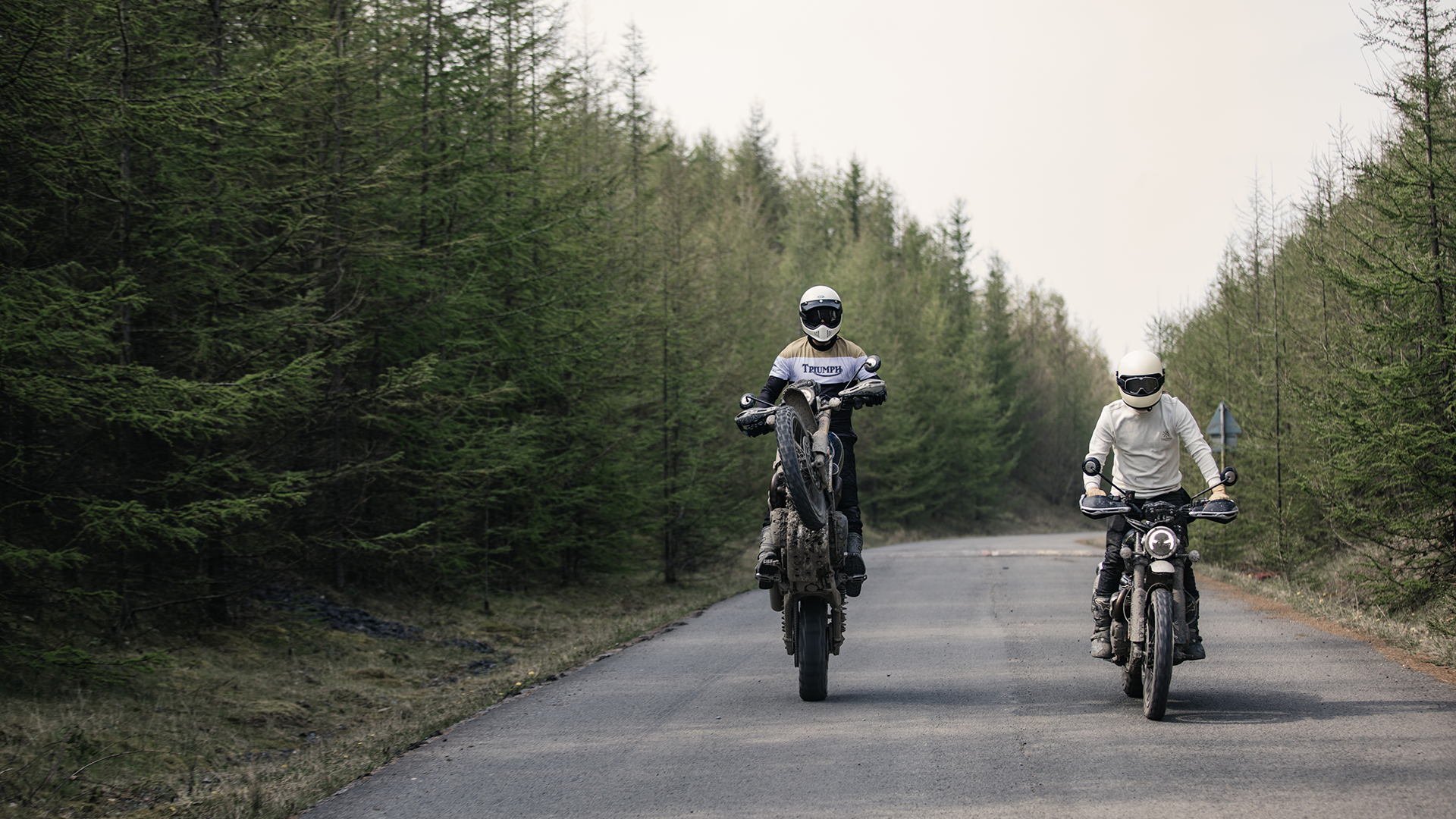 Triumph's collaboration with Bike Shed featuring two Scrambler 1200s with one doing a wheelie