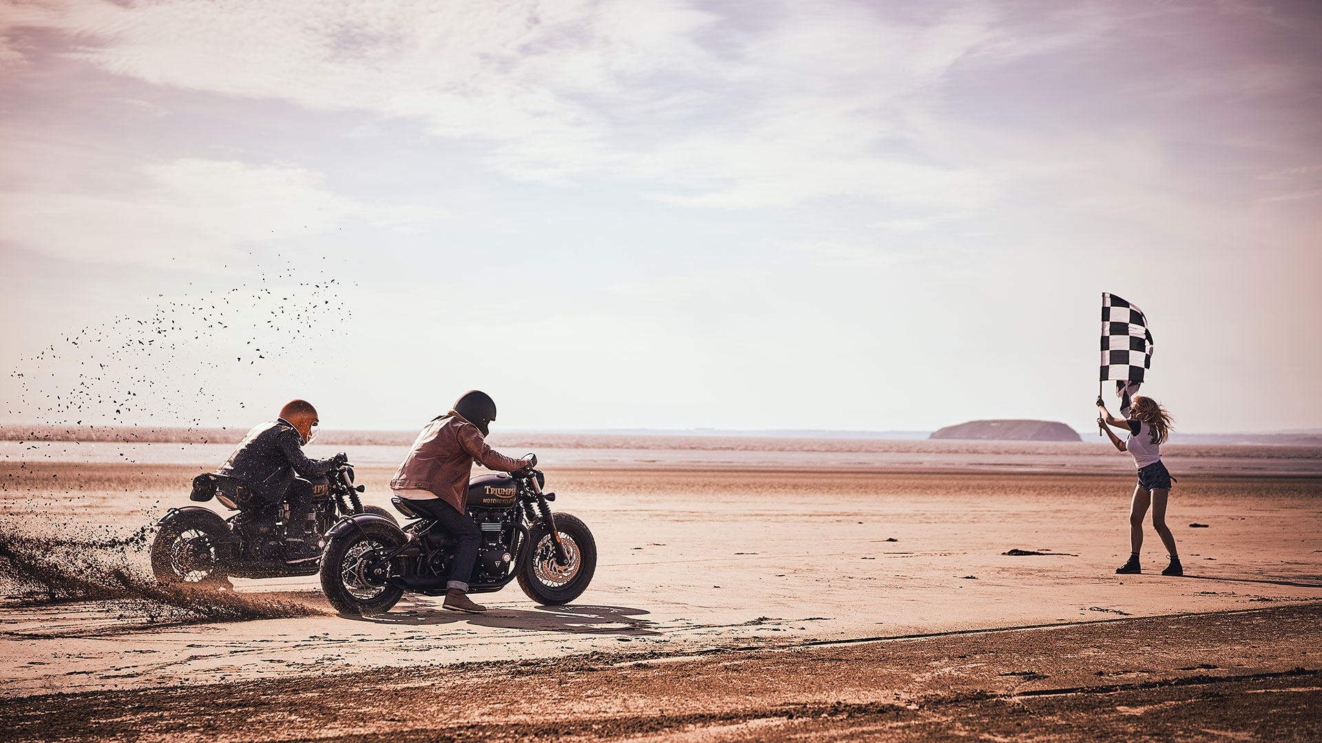 Two male model wearing Triumph SS20 lifestyle clothing collection racing two Triumph Bonneville Bobber Blacks across a beach in summer