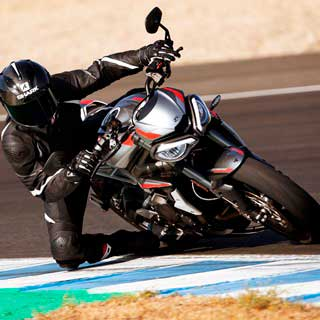 Rider on new Triumph Street Triple RS in Silver Ice with his knee down corning on the racetrack
