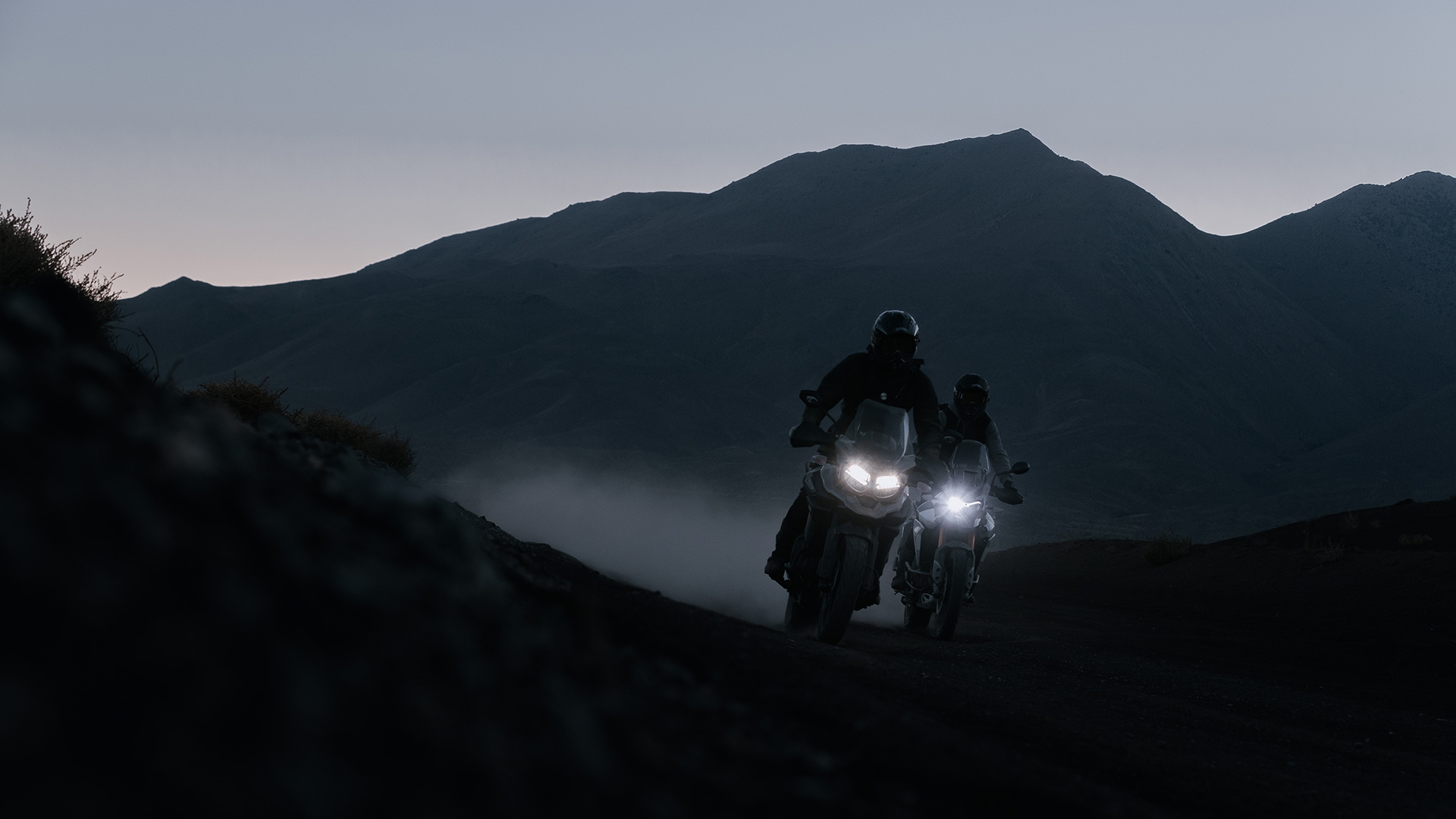 Two Triumph Tigers riding across the desert