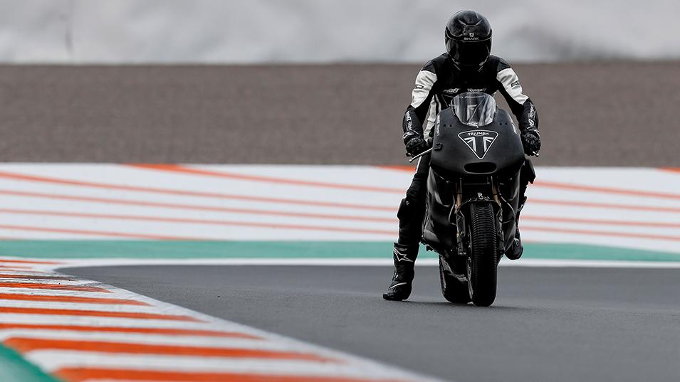 Rider stationary on Valencia MotoGP circuit, poised to ride the Triumph Moto2 prototype motorbike
