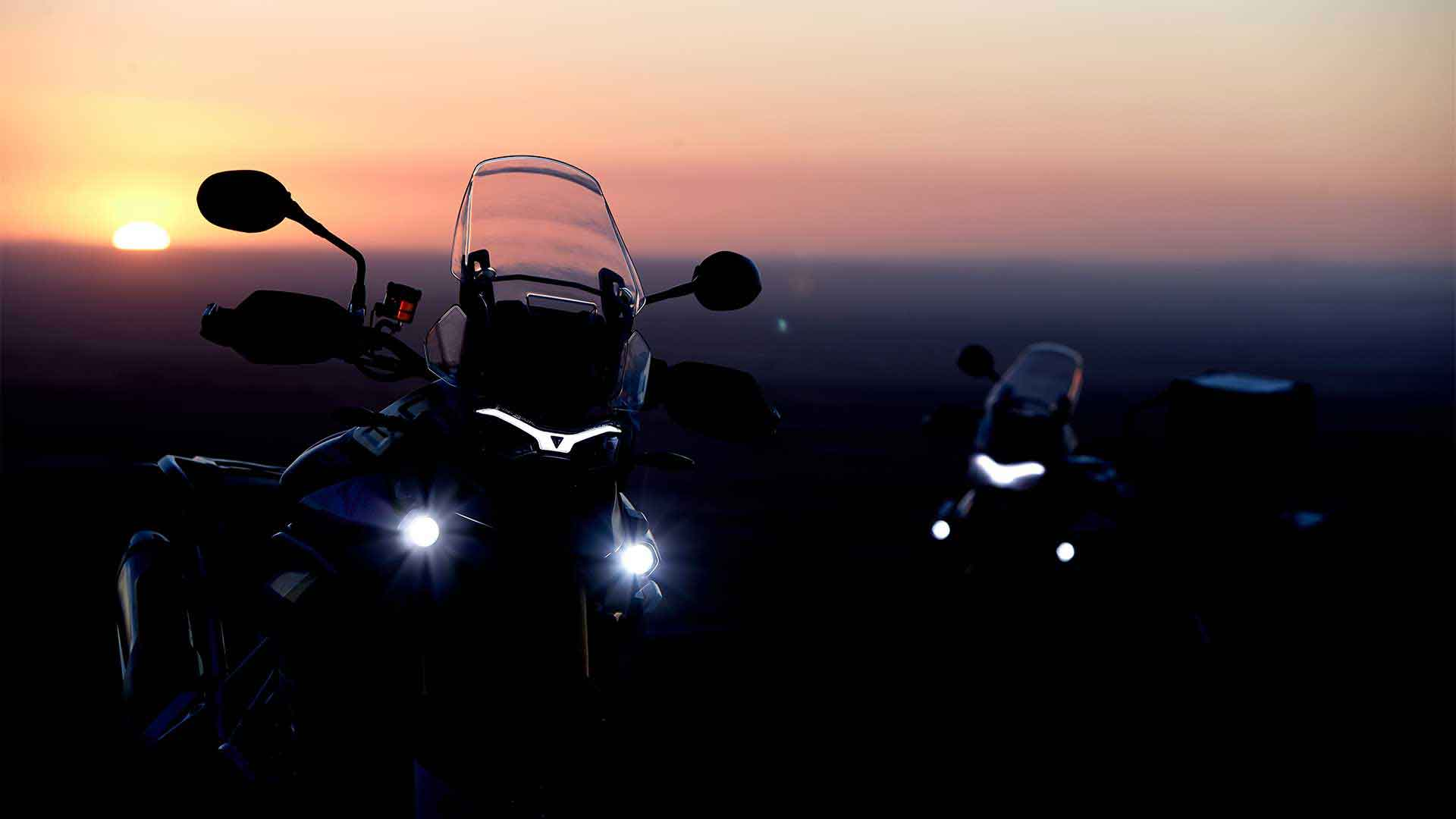 Triumph Tiger 900 silhouettes with headlights lit in sunset