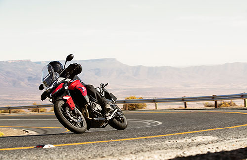 A Korosi Red Tiger 900 GT Pro taking a bend in the road