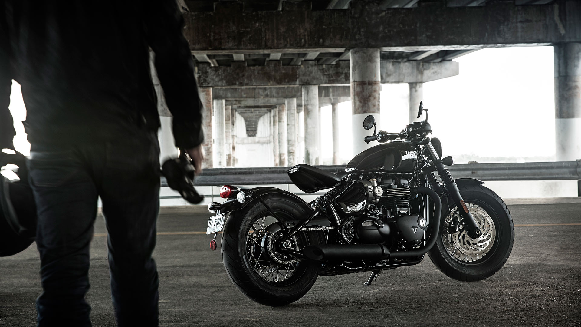 person walking towards a Triumph Bonneville Bobber Black