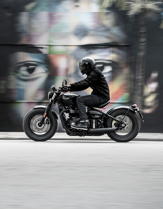 Person riding a Triumph Bonneville Bobber Black in front of street art