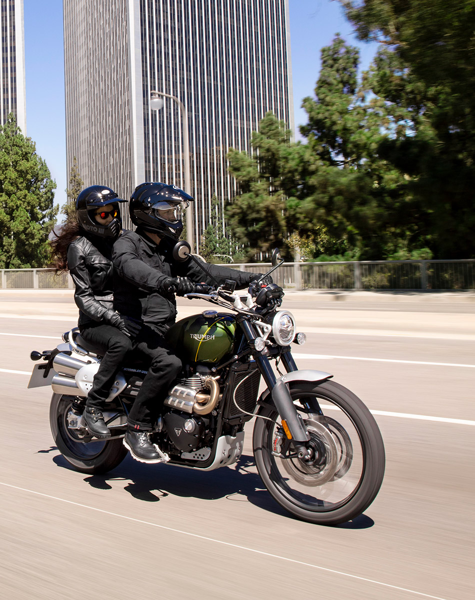 Two riders riding the class-leading Triumph Scrambler 1200 XC along an urban road, highlighting the bikes all-purpose laid back riding style