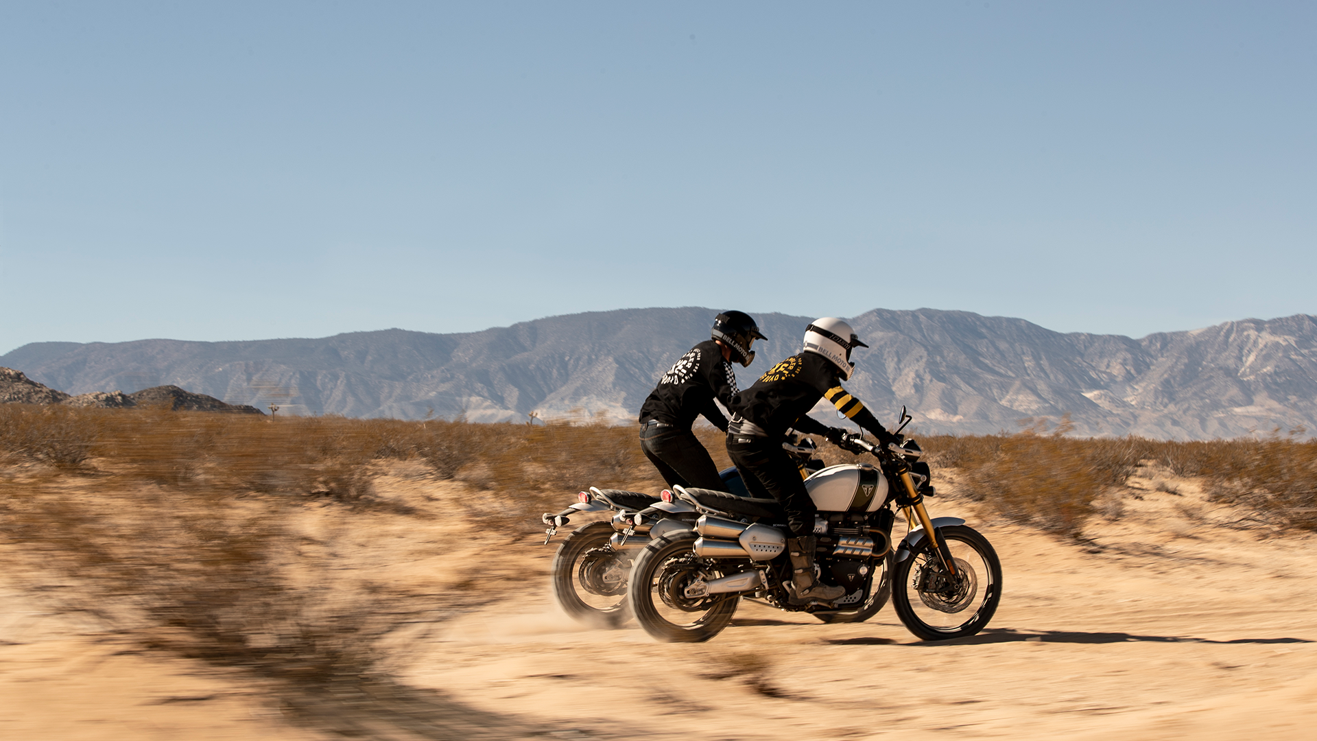 Two Triumph Scrambler 1200s scrambling across the dessert in extreme off-road style