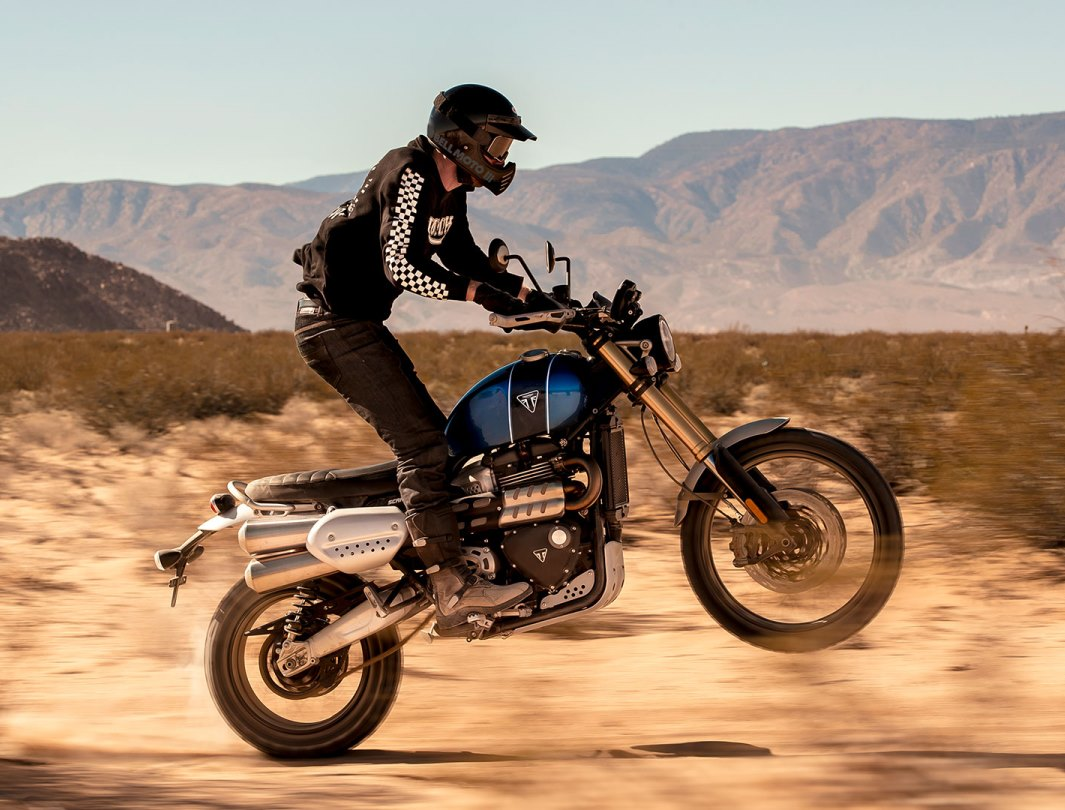 Triumph Scrambler 1200 XE scrambling across sandy plains performing a wheelie. Rider wearing limited edition Scrambler 1200 clothing