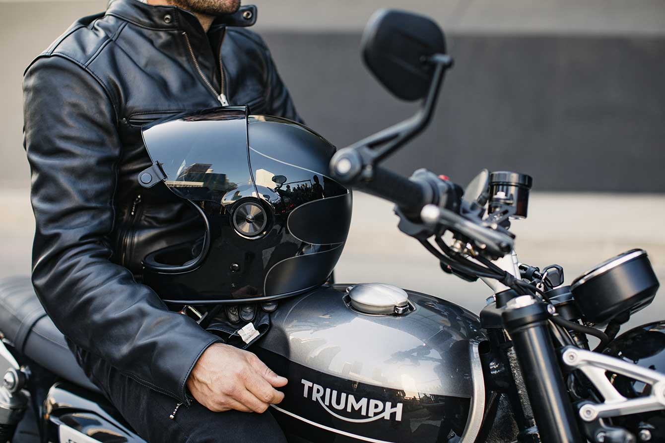 Rider poised on the all-new Triumph Speed Twin, with helmet resting on the fuel tank, ready to ride,