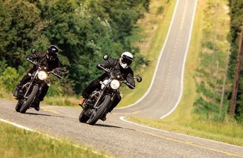 2 Triumph Street Scramblers taking a corner on road