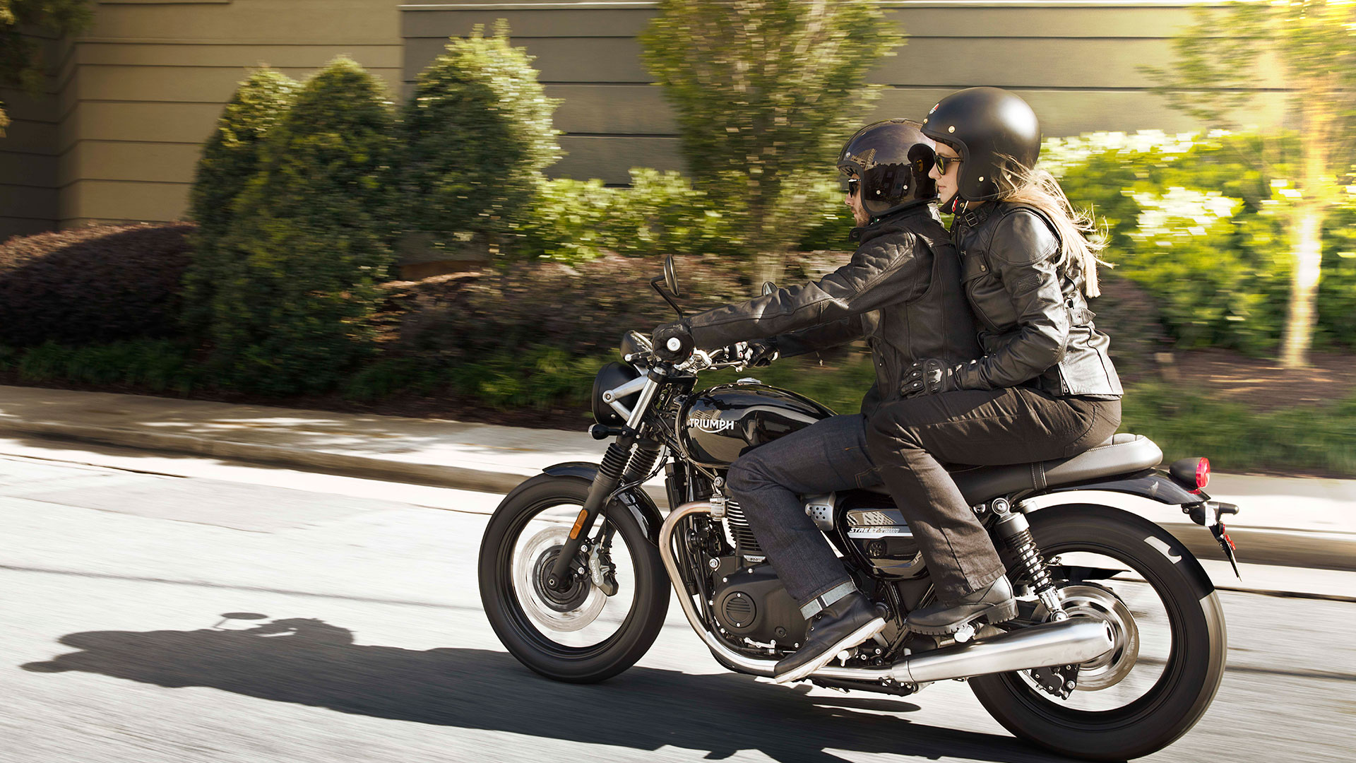 Two people riding a Triumph Street Twin in an urban setting