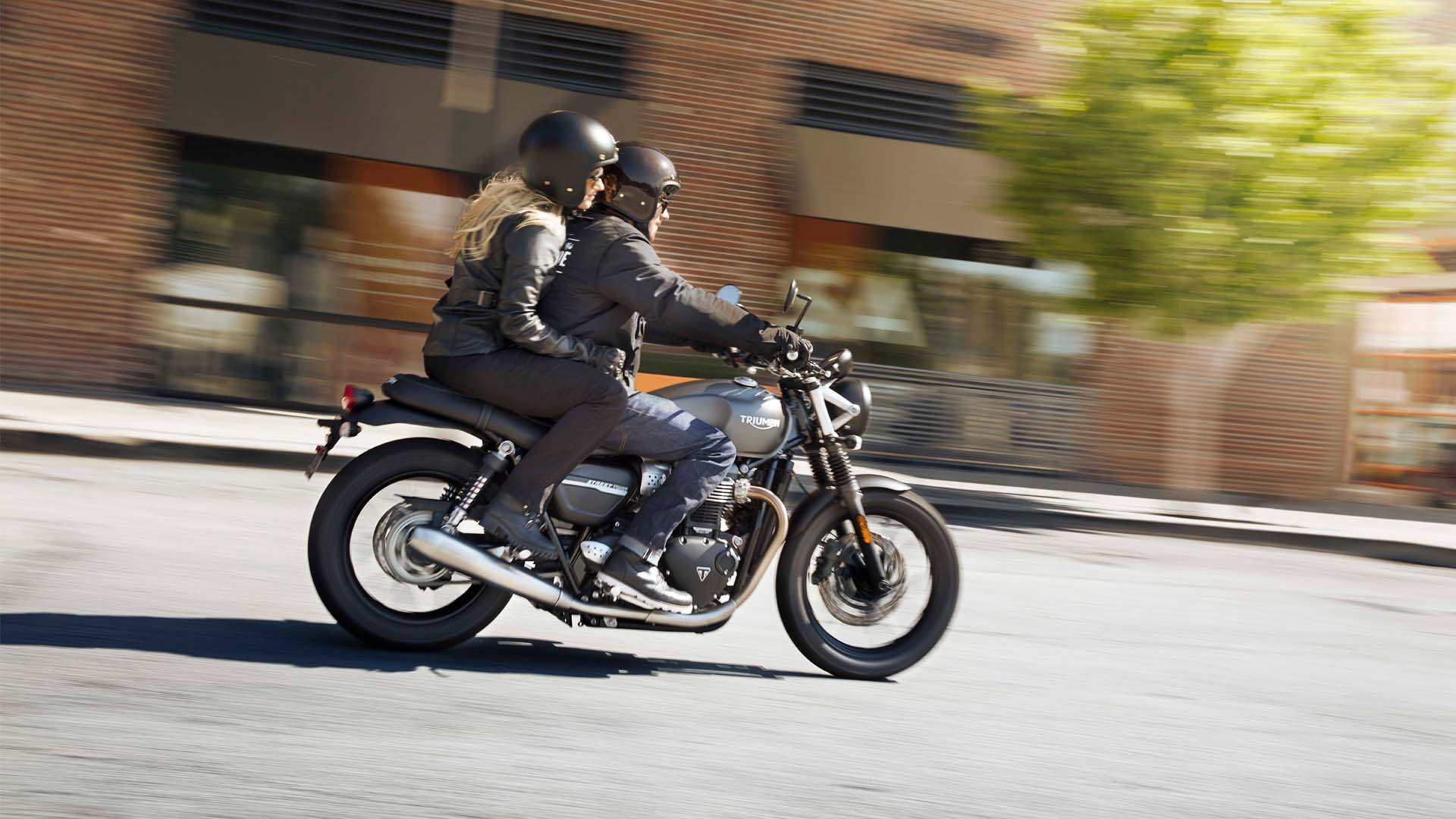 Rider and pillion on a Triumph Street Twin riding through urban setting