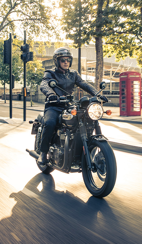 Triumph bonneville t100 black ridden by man through city