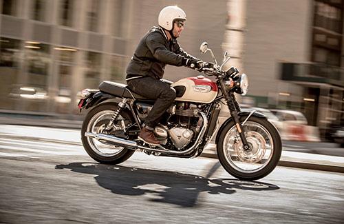 Triumph Bonneville T100 in white and orange colour variant riding through urban setting