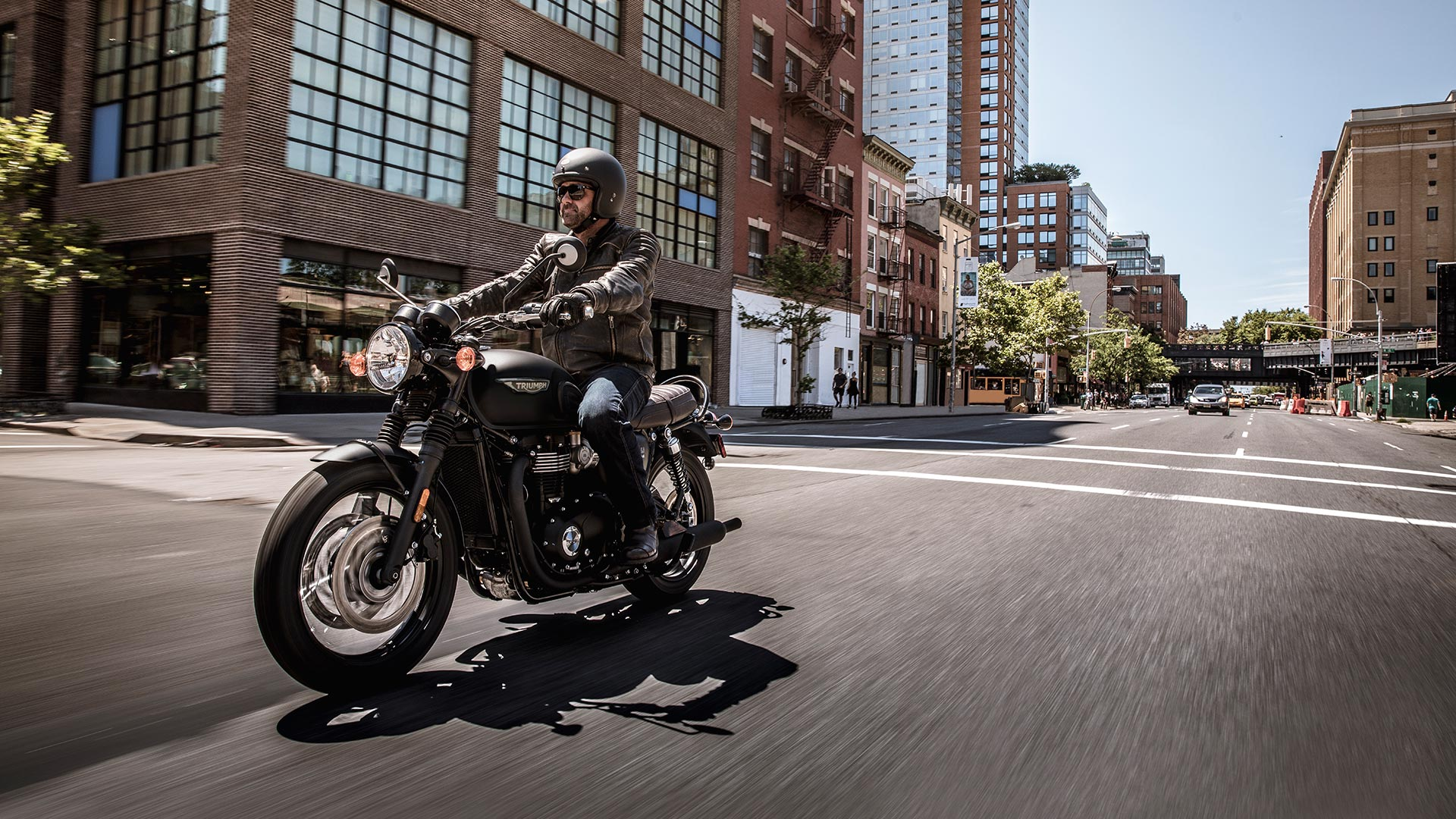 Triumph bonneville T120 black riding through city