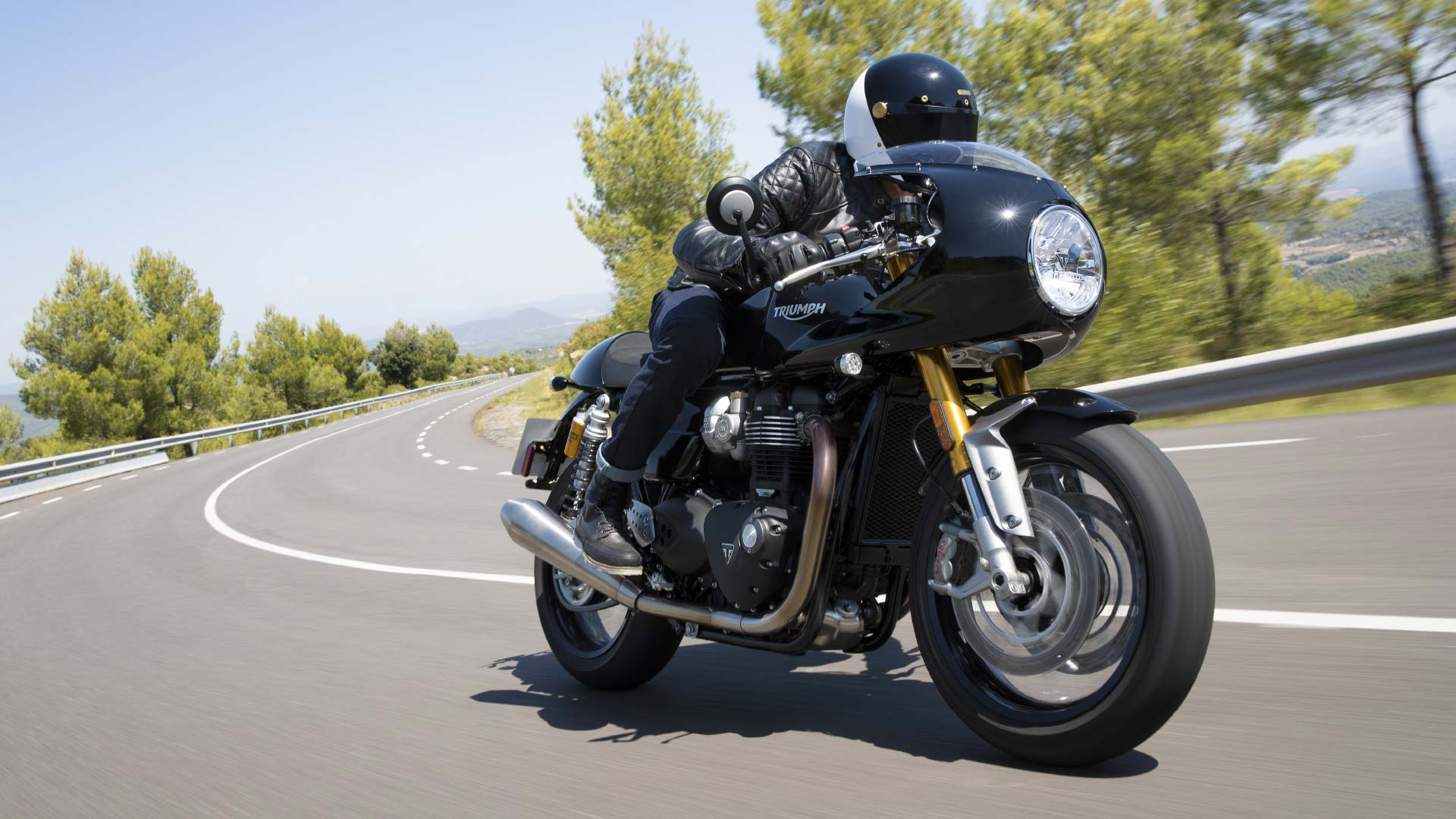 Action shot of the new Triumph Thruxton RS in Jet Black with fairing accelerating through scenic views