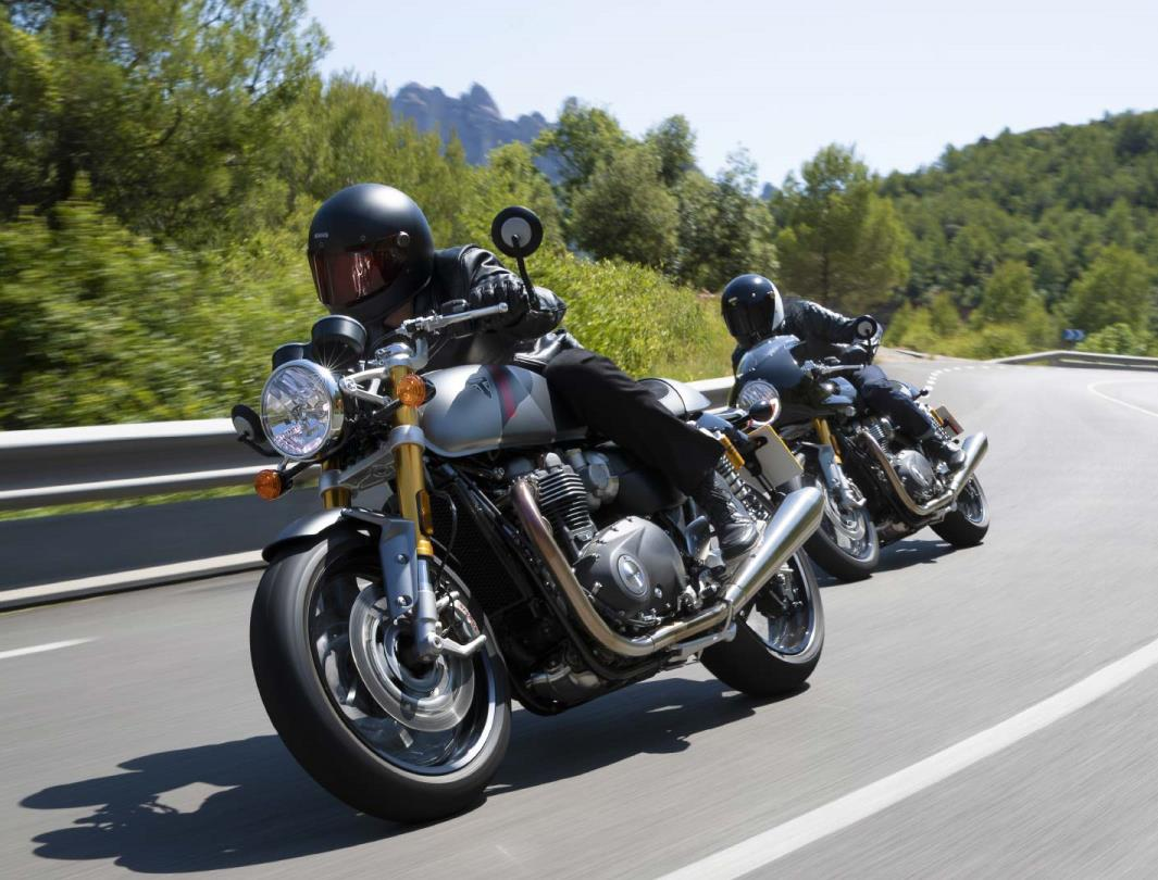 Triumph Thruxton RS motorcycle riders cornering together on their mountainous road adventure