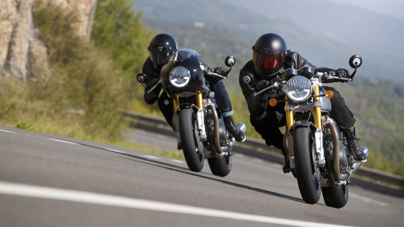 Action shot of two new Triumph Thruxton RS motorcycles cornering through mountainous roads