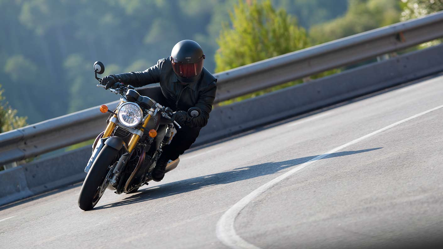 Action shot of rider cornering through mountainous roads on the new Triumph Thruxton RS