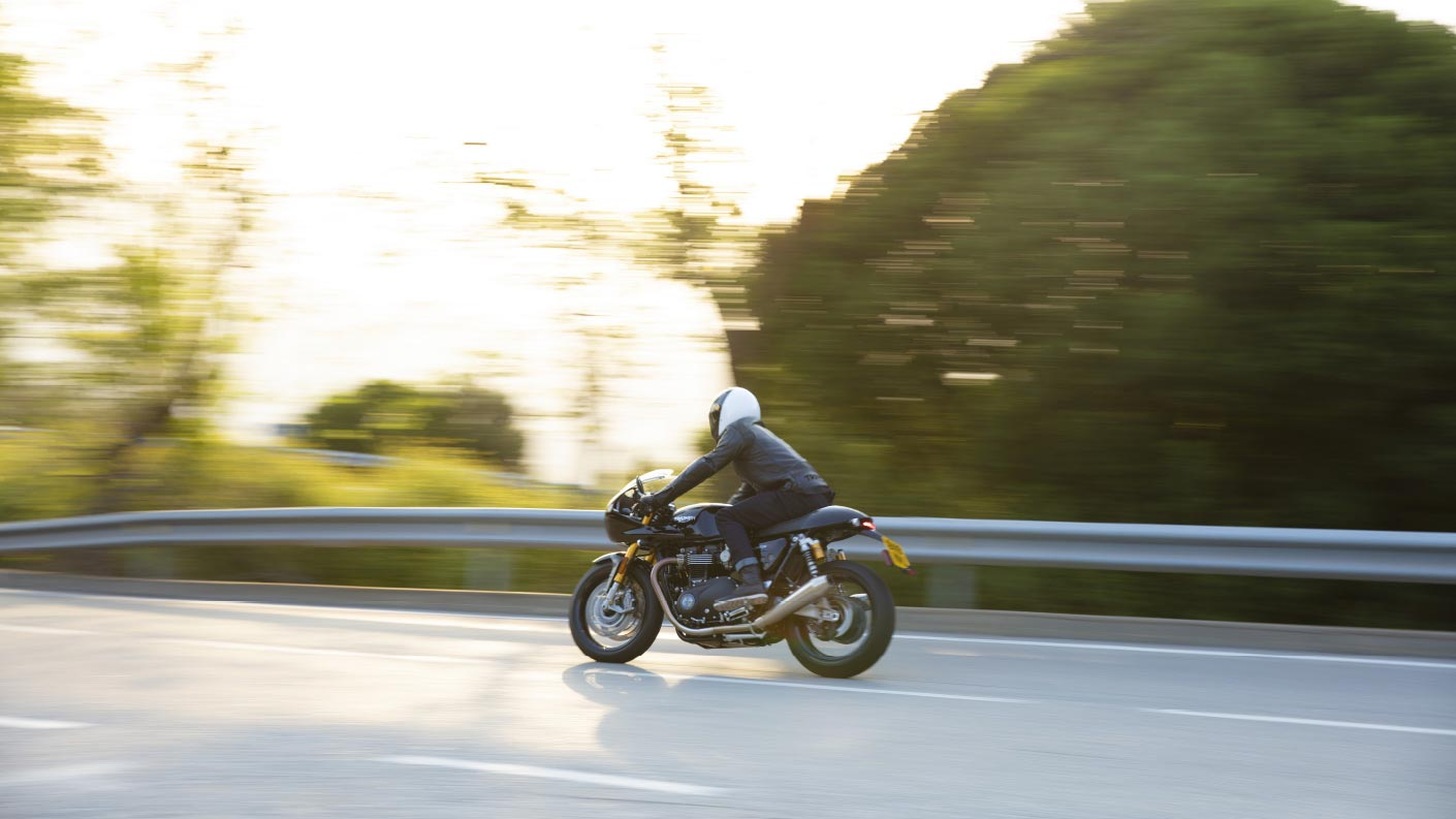 Action shot of the new Triumph Thruxton RS with fairing in Jet Black riding down a mountainous road