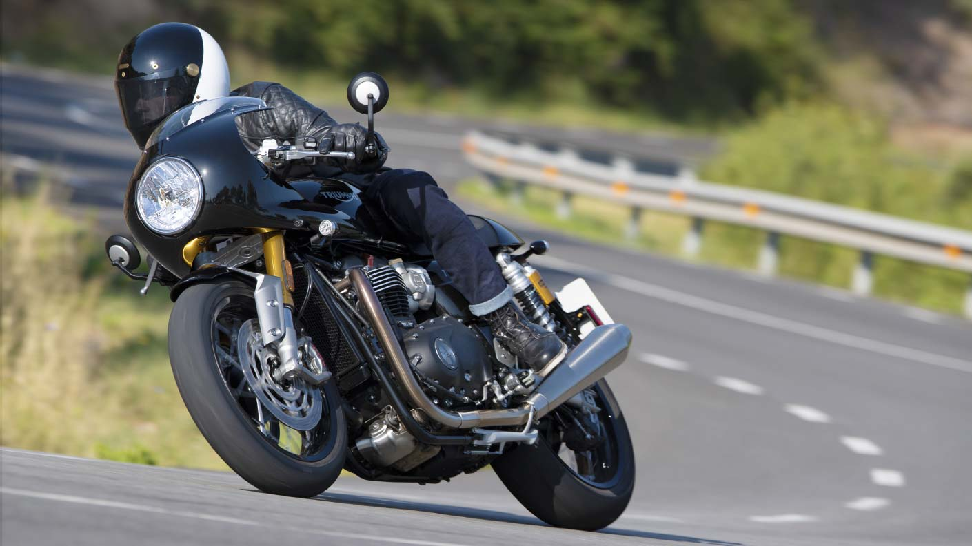 Action shot of the new Triumph Thruxton RS with fairing in Jet Black riding through mountainous roads