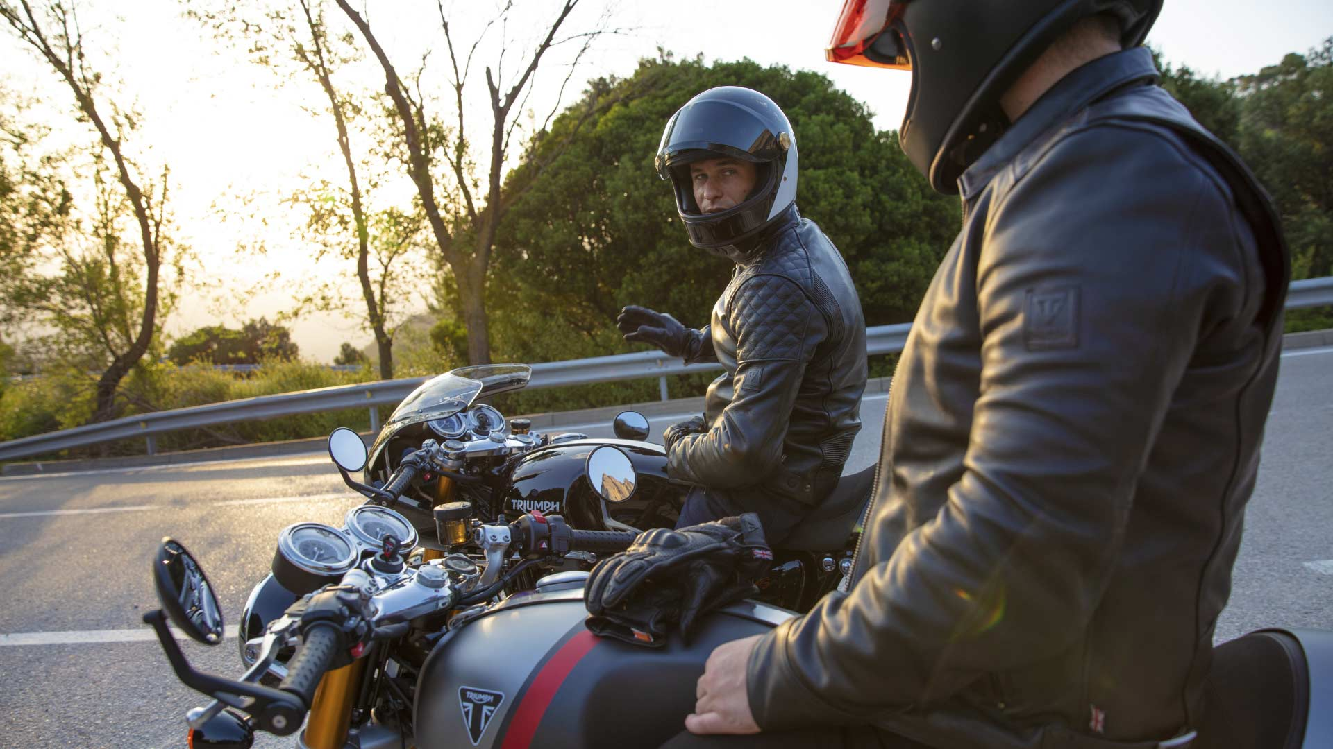 Two riders taking a moment to chat together on their Triumph Thruxton RS motorcycles