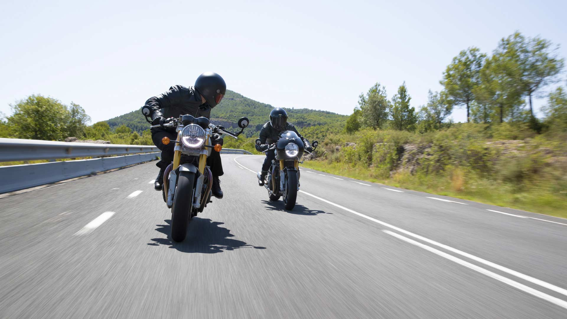 Front shot of two Triumph Thruxton RS motorcycles riding down a straight road
