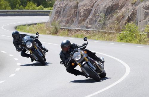 Action shot of two new Triumph Thruxton RS motorcycles flowing through mountainous corners