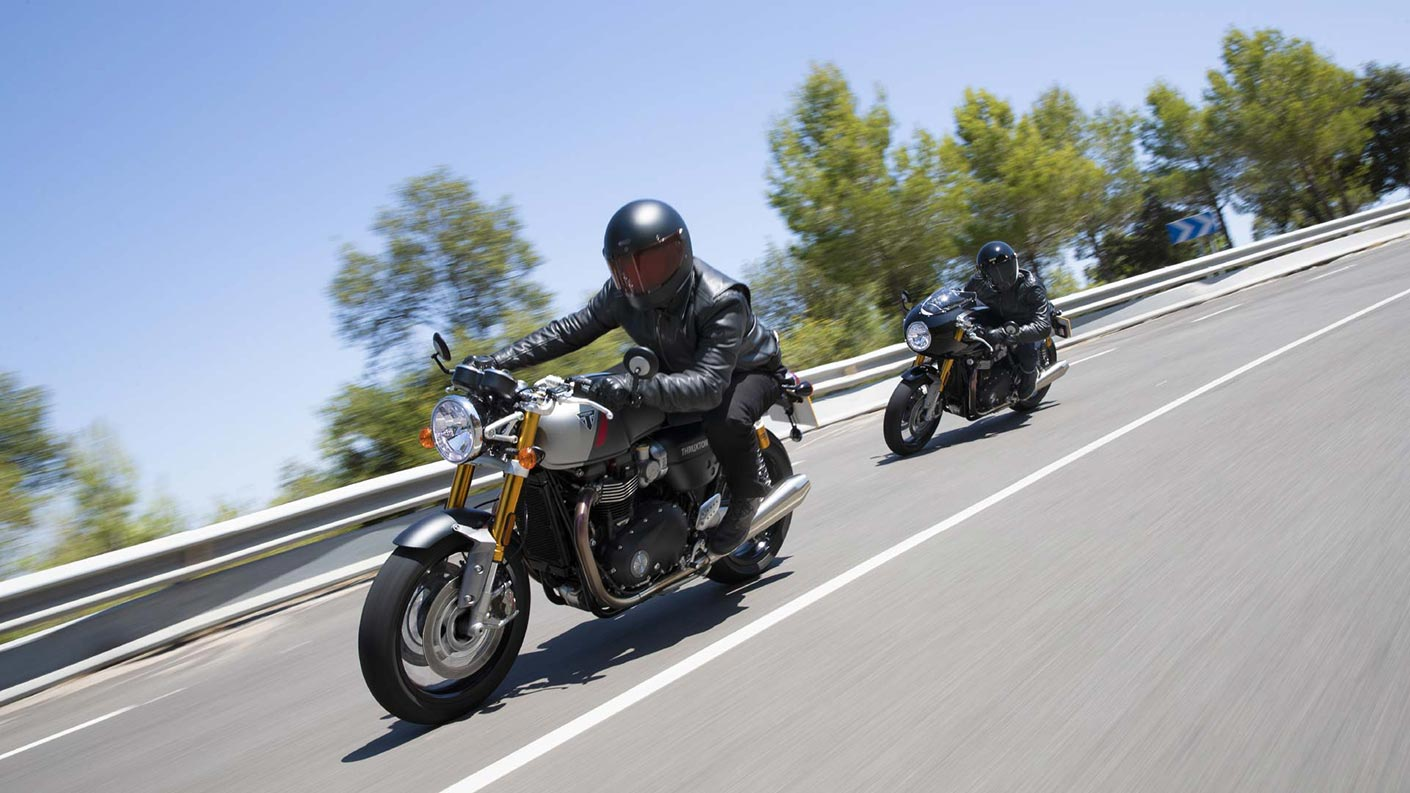 Action shot of Triumph Thruxton RS motorcycles riding down a road together