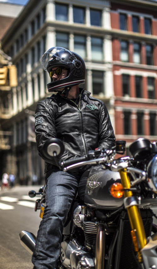 Triumph Bonneville Thruxton and rider stationary in urban setting.