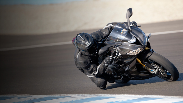 Rider racing a Triumph Daytona Moto2TM 765 motorcycle (EU and Asia Edition) around a race track in Spain