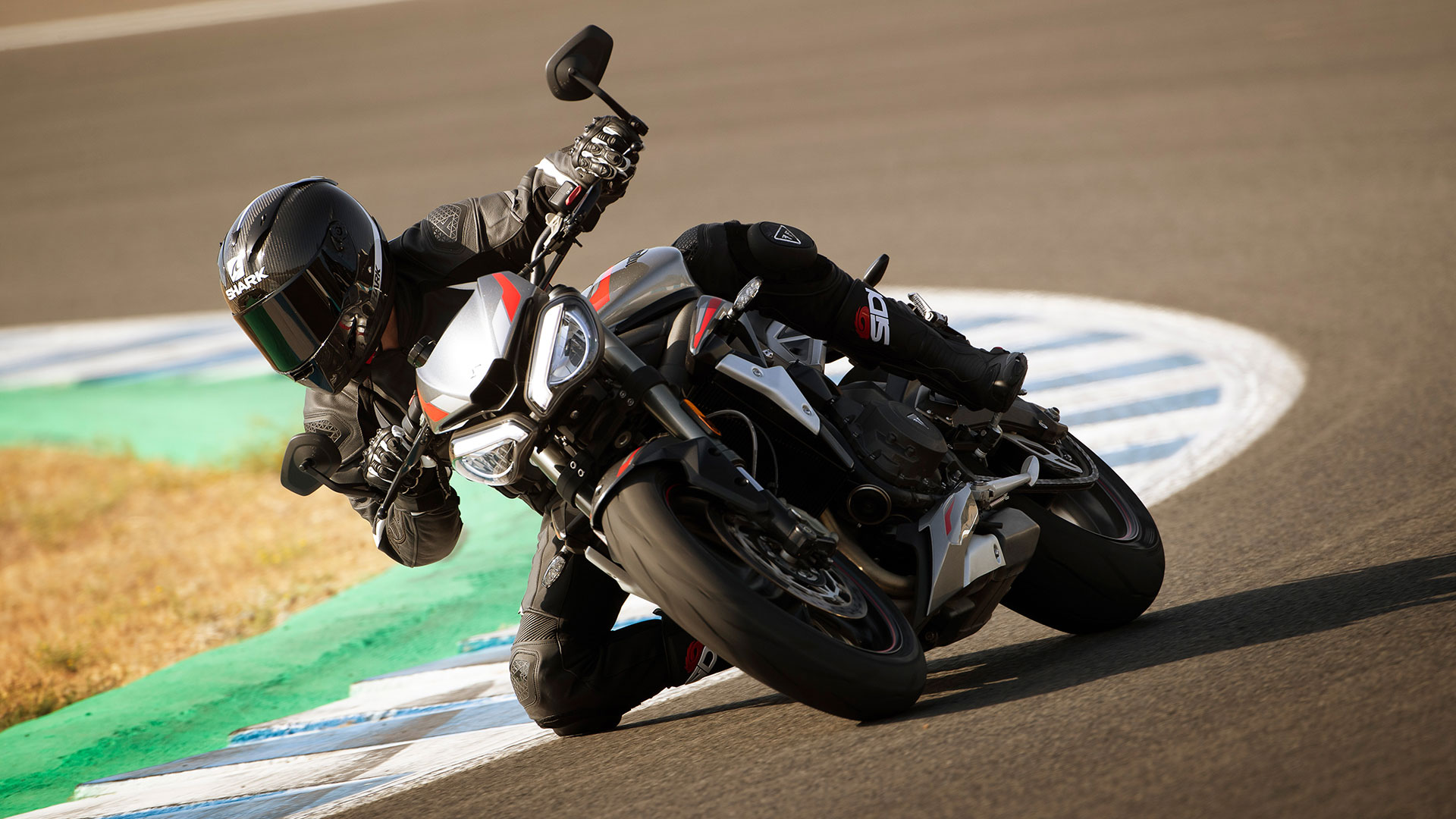 Action shot of Triumph Street Triple RS in Silver Ice powering through a corner