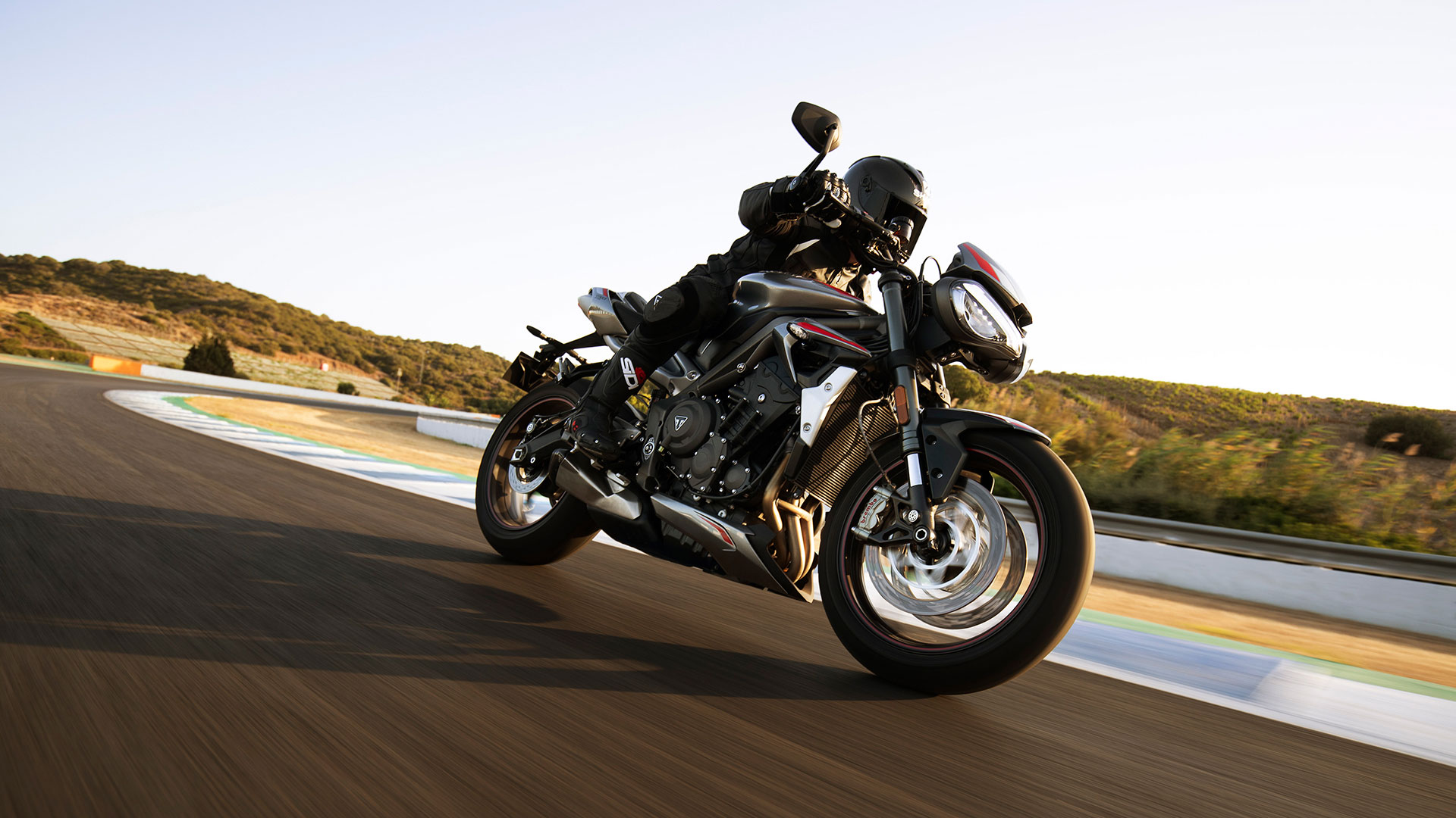 New Triumph Street Triple RS in Silver Ice powering down a racetrack