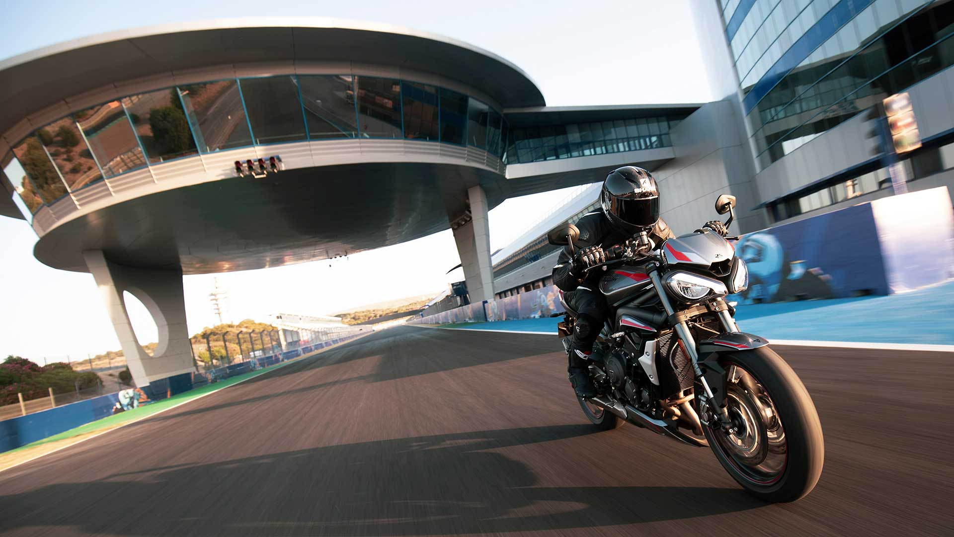 Rider on new Triumph Street Triple RS in Silver Ice powering down a racetrack straight