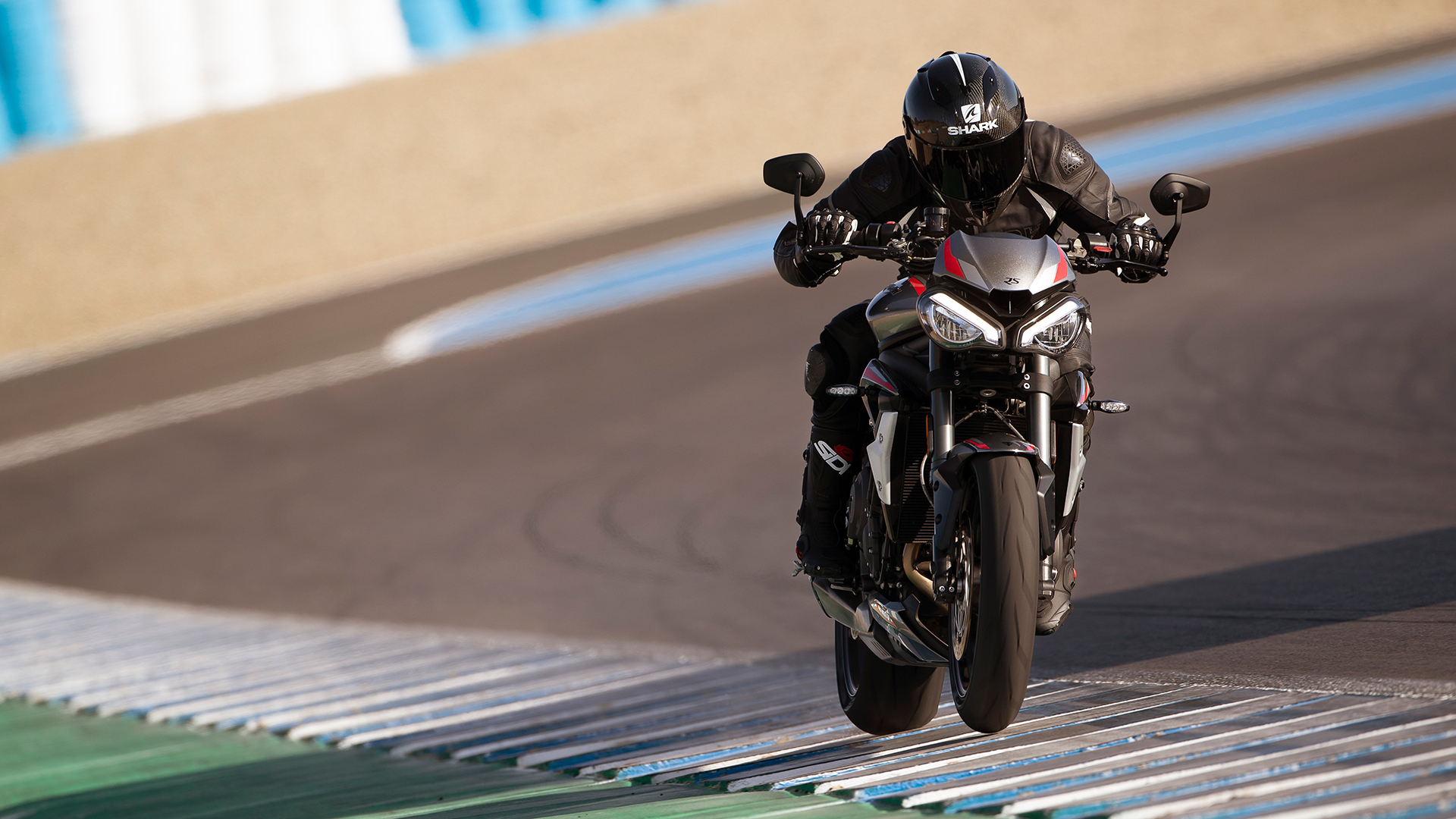 Action shot of rider on new Triumph Street Triple RS in Silver Ice powering down a racetrack