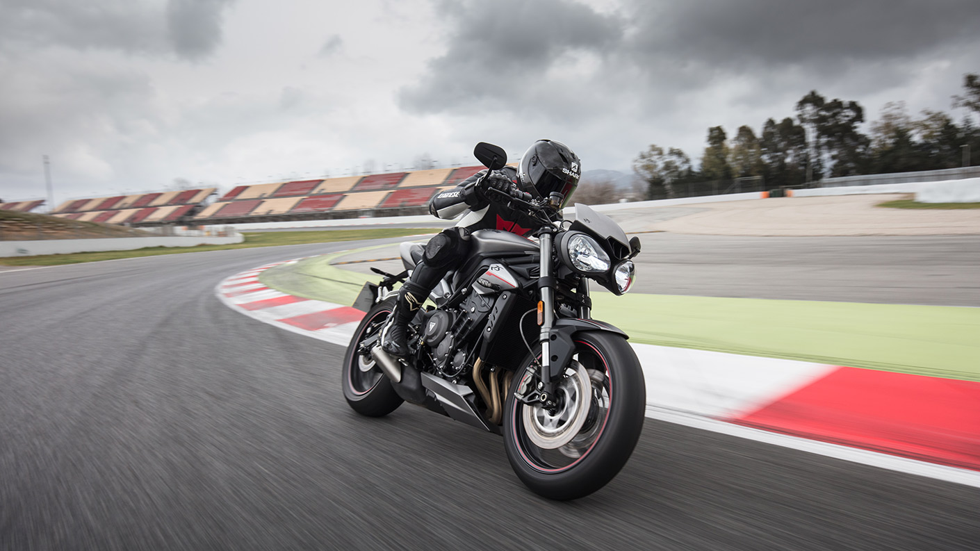 Triumph Street Triple motorcycle cornering around bend on race track