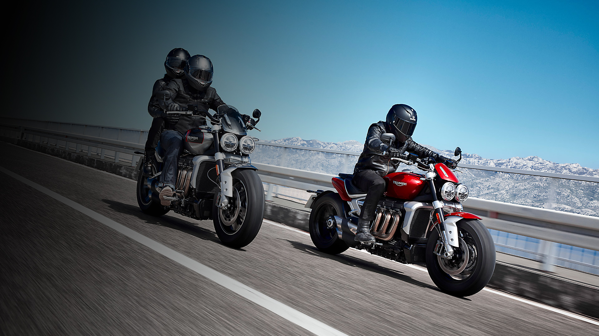 Action shot of rider and pillion on a Silver Ice & and Grey Triumph Rocket 3 GT alongside rider on a Korosi Red Triumph Rocket 3 R