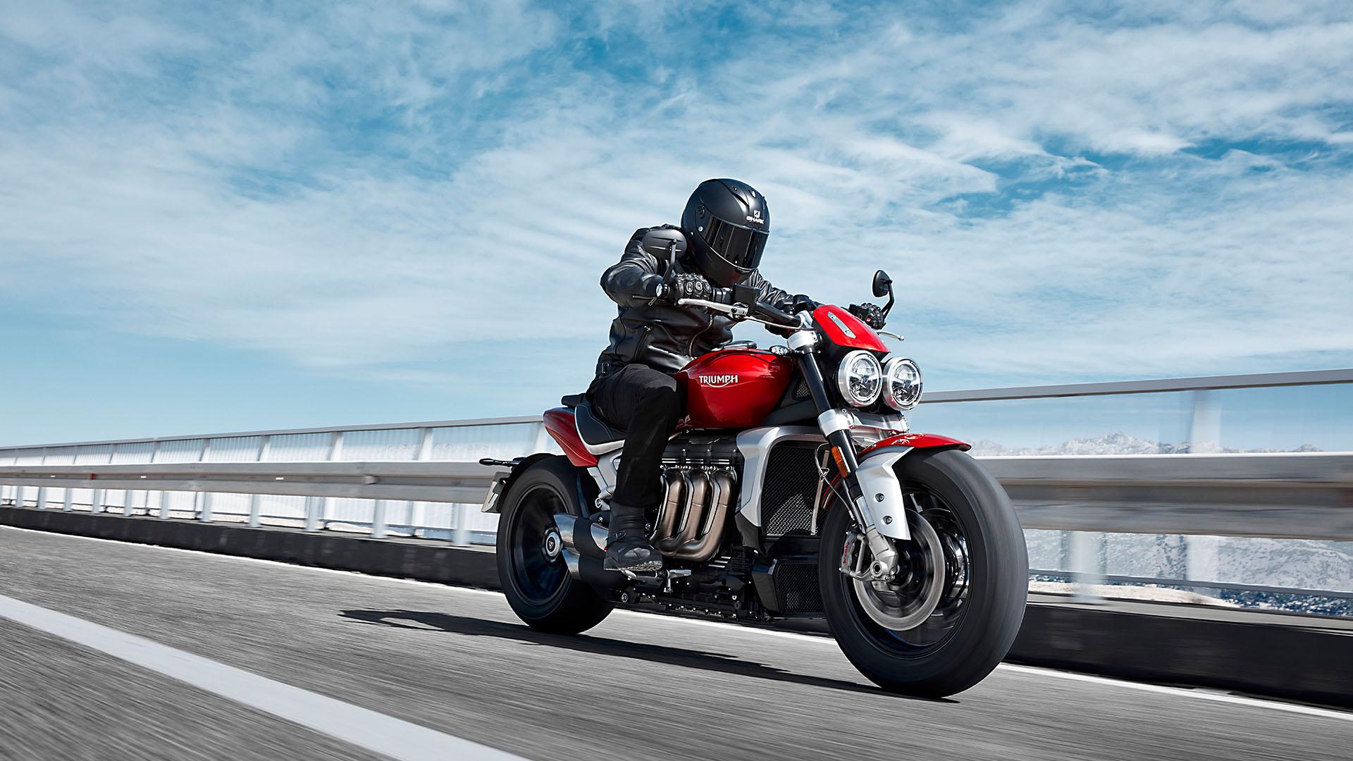 Triumph new Rocket 3 R in Korosi Red riding swiftly on a road that runs through a mountainous terrain