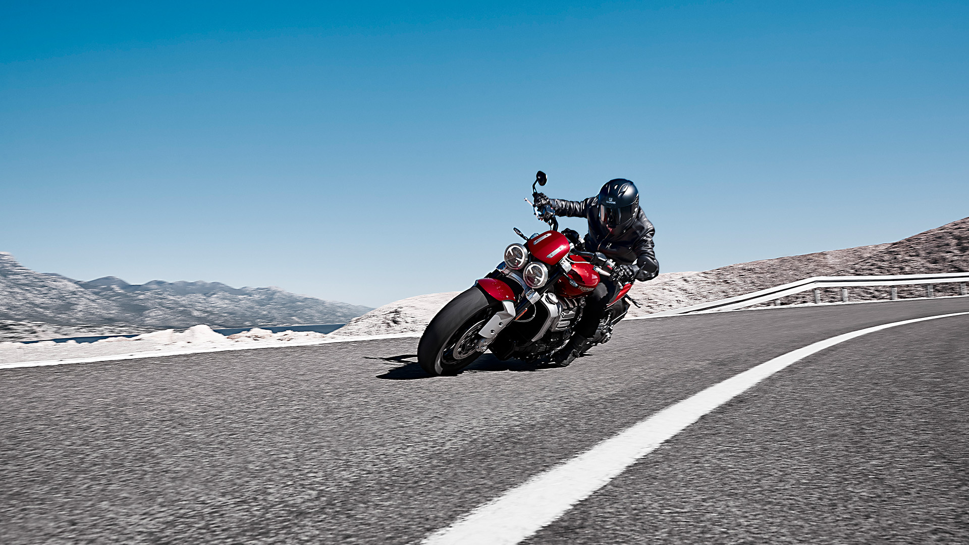 A rider cornering a scenic route on the new Triumph Rocket 3 R in Korosi Red