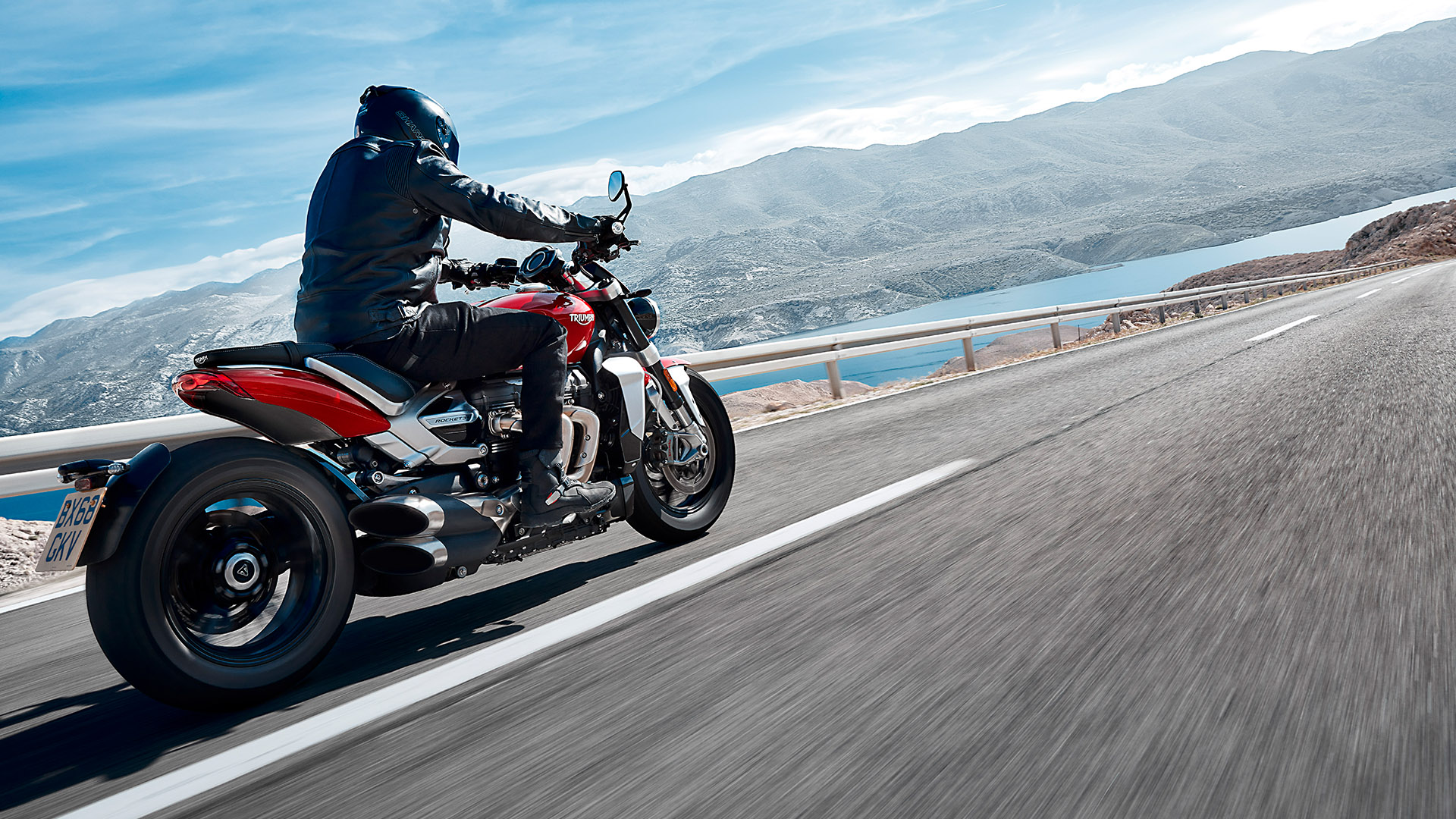 A rider on the Triumph Rocket 3 R travelling down a straight road
