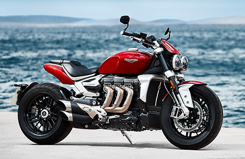 Triumph Rocket 3 R in Koroshi Red muscular and magnificent side profile at seafront