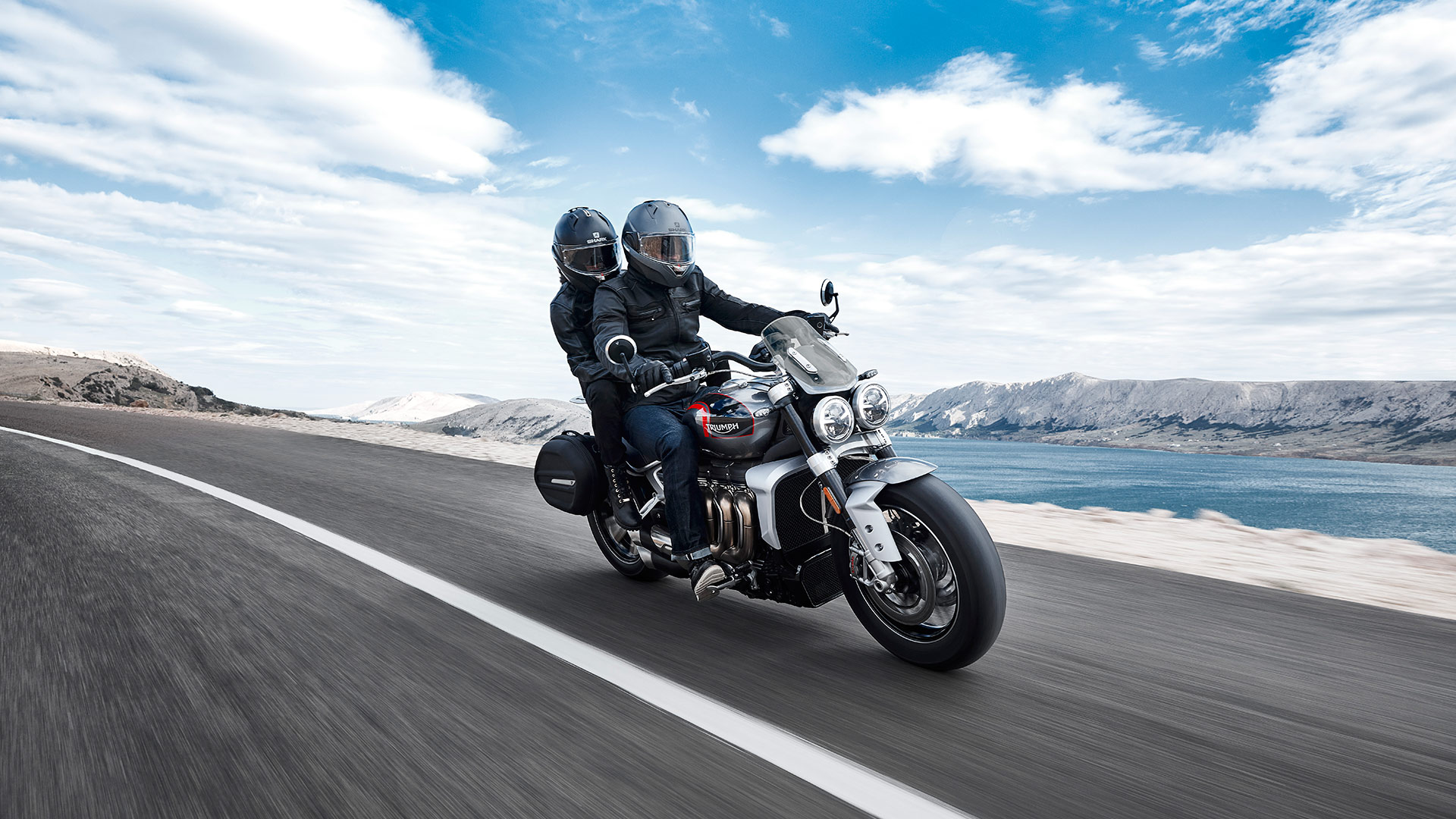 Triumph Rocket 3 GT in aluminium silver and storm grey, fitted with accessories including; black sports pannier with Triumph badging and screen, travelling along a straight road