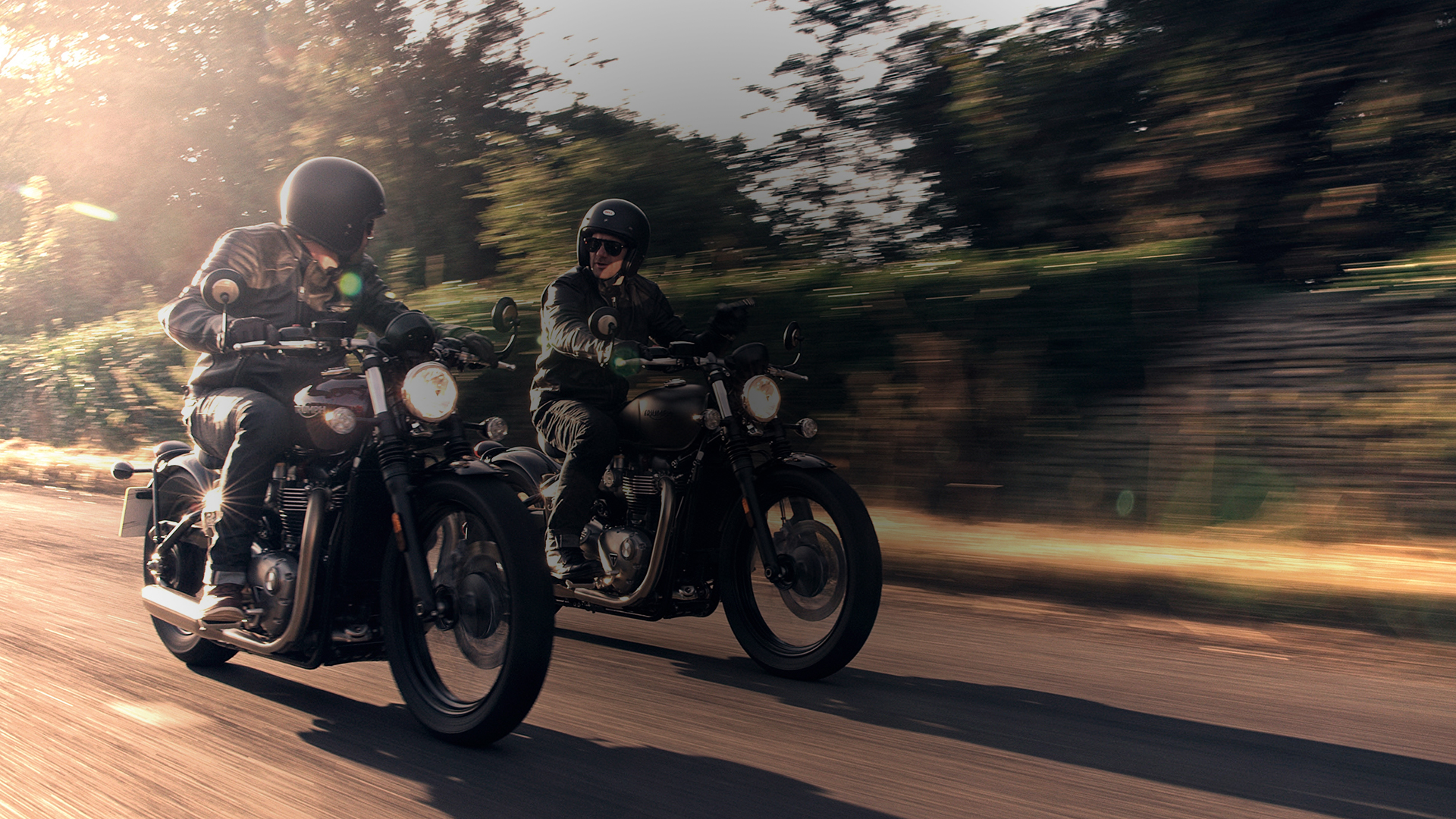Two people riding Triumph Bobbers through a street.