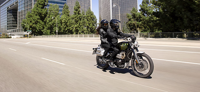 Two people riding on a Scrambler 1200 through a city.