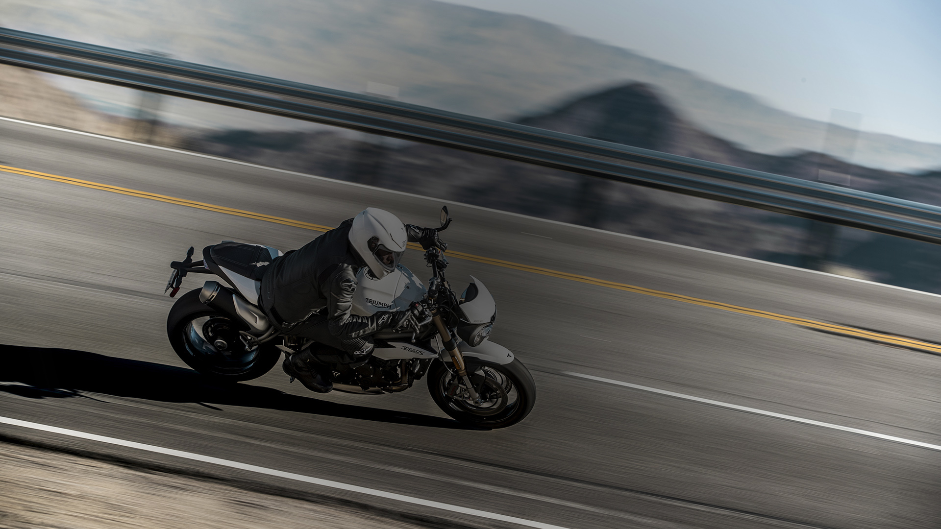 Person riding a Speed Triple through a corner in the mountains.
